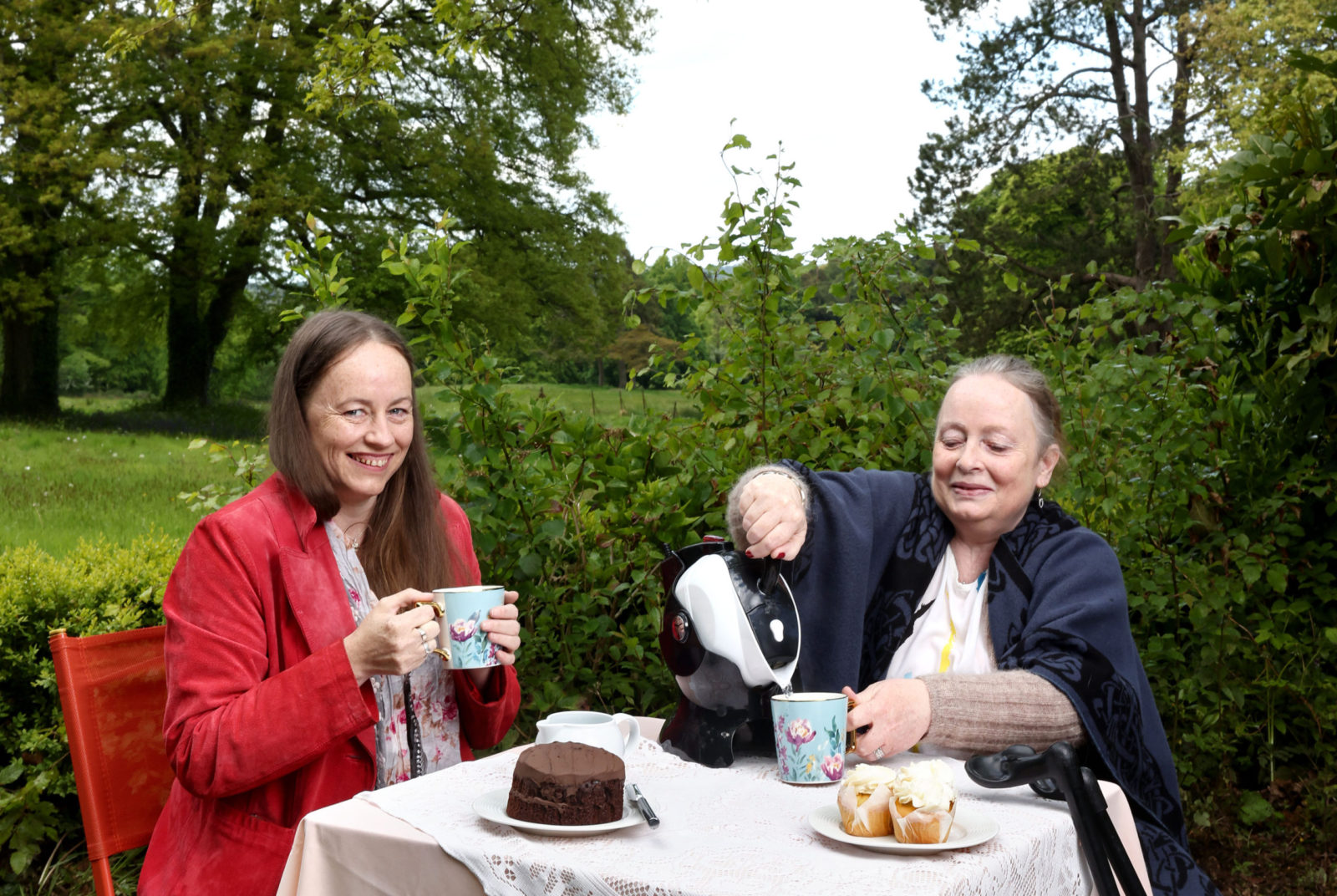 Mother and Daughter sitting in the garden having tea with their Uccello Kettle