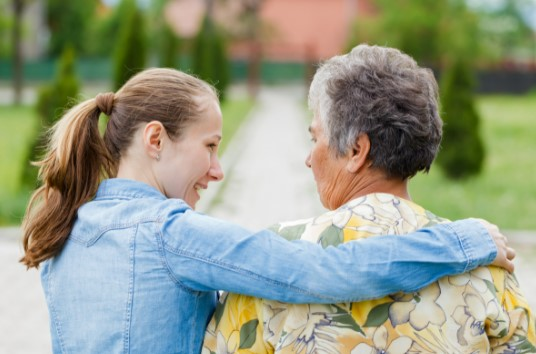 Young woman caring for elderly woman